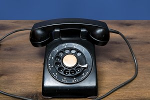 Antique old rotary dial telephone on wooden desk