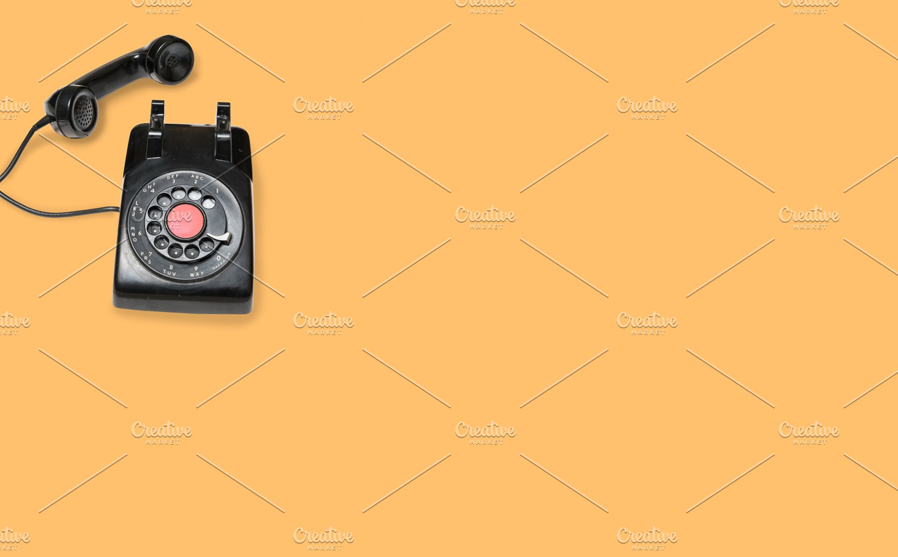 Antique old rotary dial telephone on orange background