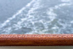 Raindrops on teak rail of cruise ship at sea