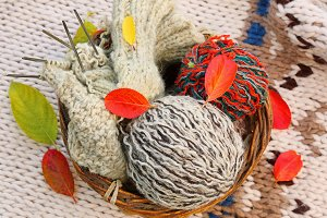 basket with balls of wool for knitting with autumn leaves rural retro style