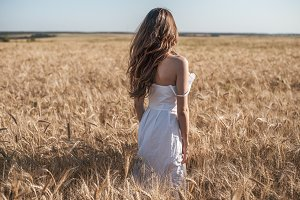 Girl in a white dress field, wheat outdoor recreation, beautiful dress. A woman is walking outdoors.