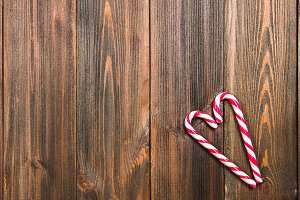 Christmas candy canes in the shape of a heart on a brown wooden table. Copy space.