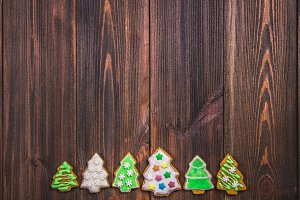 Christmas gingerbread cookies in the shape of Christmas trees on a brown wooden table. Copy space.