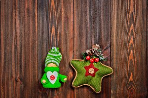 Christmas toys in Scandinavian style on a brown wooden table. Green knitted star and wooden girl in knitted clothes. Copy space.