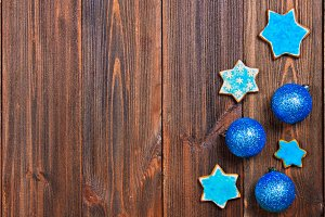 Christmas gingerbread cookies of a blue star with Christmas balls on a brown wooden table. Copy space.