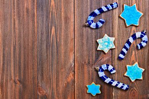 Christmas gingerbread cookies of a blue star with Christmas tree decorations on a brown wooden table. Copy space.