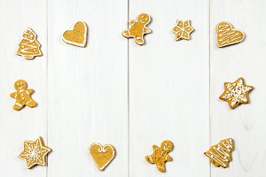 Christmas gingerbread cookies of different shapes on a white wooden table. Copy space.