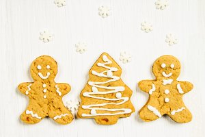 Gingerbread men friends at the Christmas tree on a white wooden table.