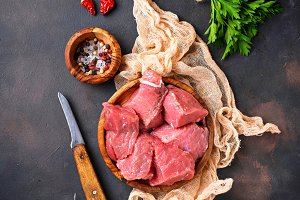 Raw chopped meat with spices on rusty background