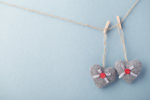 Decorated knitted hearts on blue