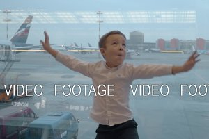 Child showing flying bird against window with airport area view
