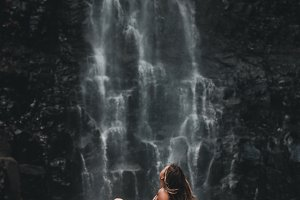 Young woman relaxing near waterfall