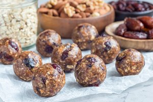 Healthy energy balls with cranberries, nuts, dates and rolled oats on parchment, horizontal