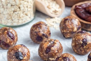 Healthy energy balls with cranberries, nuts, dates and rolled oats on parchment, vertical