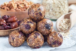 Homemade energy balls with cranberries, nuts, dates and rolled oats on parchment, horizontal
