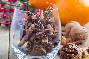 Cinnamon sticks and anise stars in glass with oranges and nuts on background, fall winter decoration, square