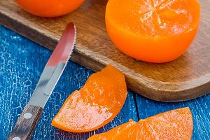 Cut persimmon fruits on wooden board and table, ready to eat, square