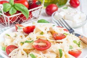 Pasta salad with tie pasta, feta cheese, cherry tomatoes, mustard and basil, square