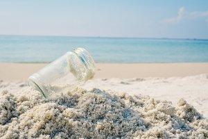 Glass jar on white sand