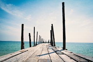 old wooden bridge in to the blue sea