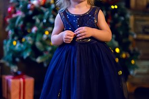 girl child blonde in the blue dress standing at the tree