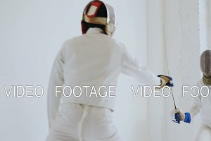 Pair of fencers having practice defence exercises in fencing in studio indoors