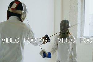 Two fencers having training attack exercises in fencing in studio