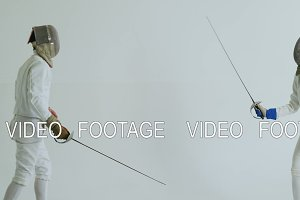 Two fencers have fencing training on white background indoors