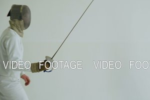 Handheld of Two fencers have fencing training on white background indoors