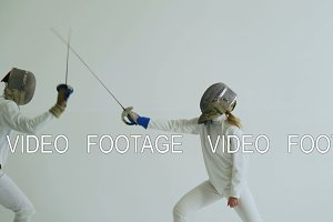 Two fencers have fencing match on white background indoors