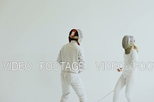 Young woman fencer having fencing training with trainer in white studio indoors