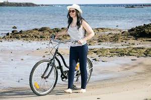 Young woman with bike on seaside
