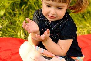 Little girl in garden talking on red carpet