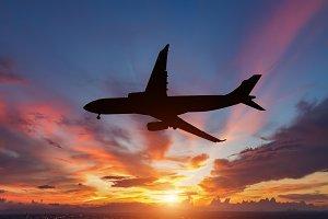 plane flying in sunset.