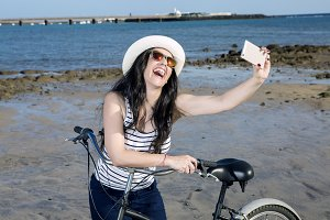 Laughing girl taking selfie on seasi
