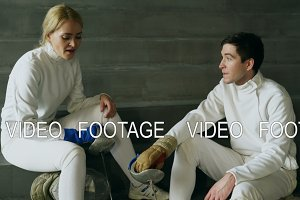 Two young fencers man and woman talking after fencing training indoors