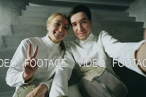 POV of Two young smiling fencers man and woman taking selfie on smartphone camera after fencing training indoors