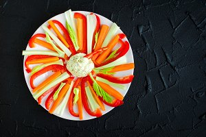 Colorful vegetable sticks in a plate with dip sauce