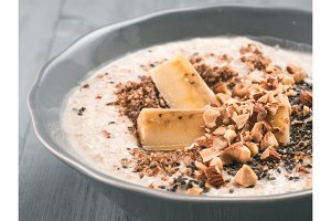Overnight oats in bowl and ingredients on gray wooden table
