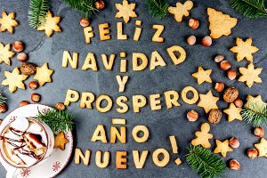 FELIZ NAVIDAD EN SPANISH COOKIES. Words Merry Christmas and happy new year en Spanish with baked cookies, Christmas card for hispanic countries top view