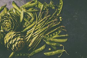 Food background with fresh green vegetables - asparagus, artichoke and green pea. Toned photo