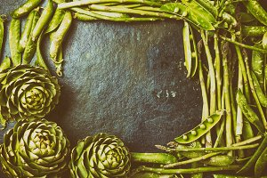 Food background with fresh green vegetables - asparagus, artichoke and green pea. Frame with copyspace. Toned photo