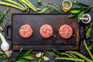 Raw meet ground beef burgers on cast iron frying board with asparagus, herb, oil and spices. Top view