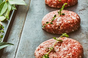 Raw meet ground beef burgers on cast iron frying board with asparagus, herb, oil and spices. Toned