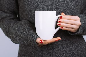 Woman holds white coffee cup