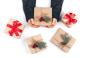 Woman's hands and three Christmas gift boxes