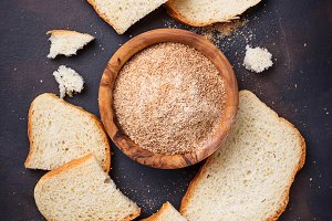 Bowl of breadcrumbs and slices of a loaf