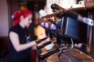 young girl Barista prepares coffee i