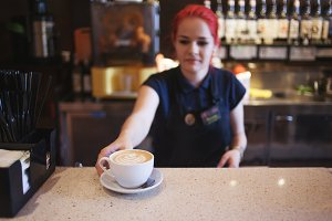 Happy girl Barista gives coffee  to
