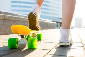 Pretty sporty lady with skateboard.